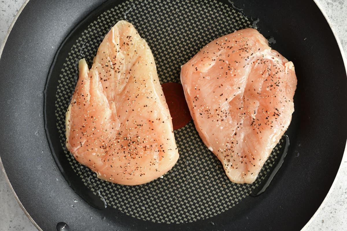 raw, seasoned chicken breasts in a pan