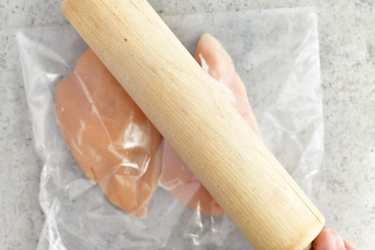 a wooden rolling pin flattening raw chicken breasts in a plastic bag
