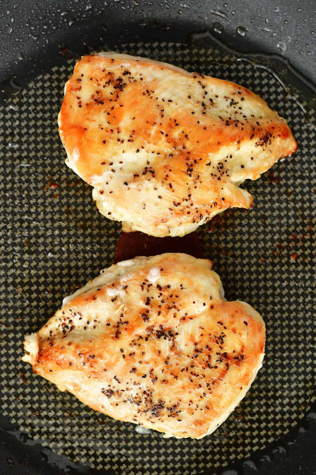 two cooked chicken breasts in a pan