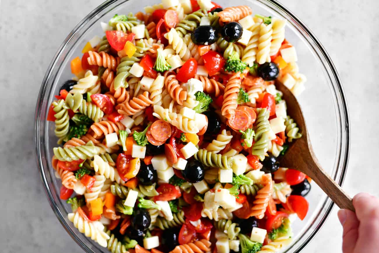 stirring the Italian pasta salad with a wooden spoon