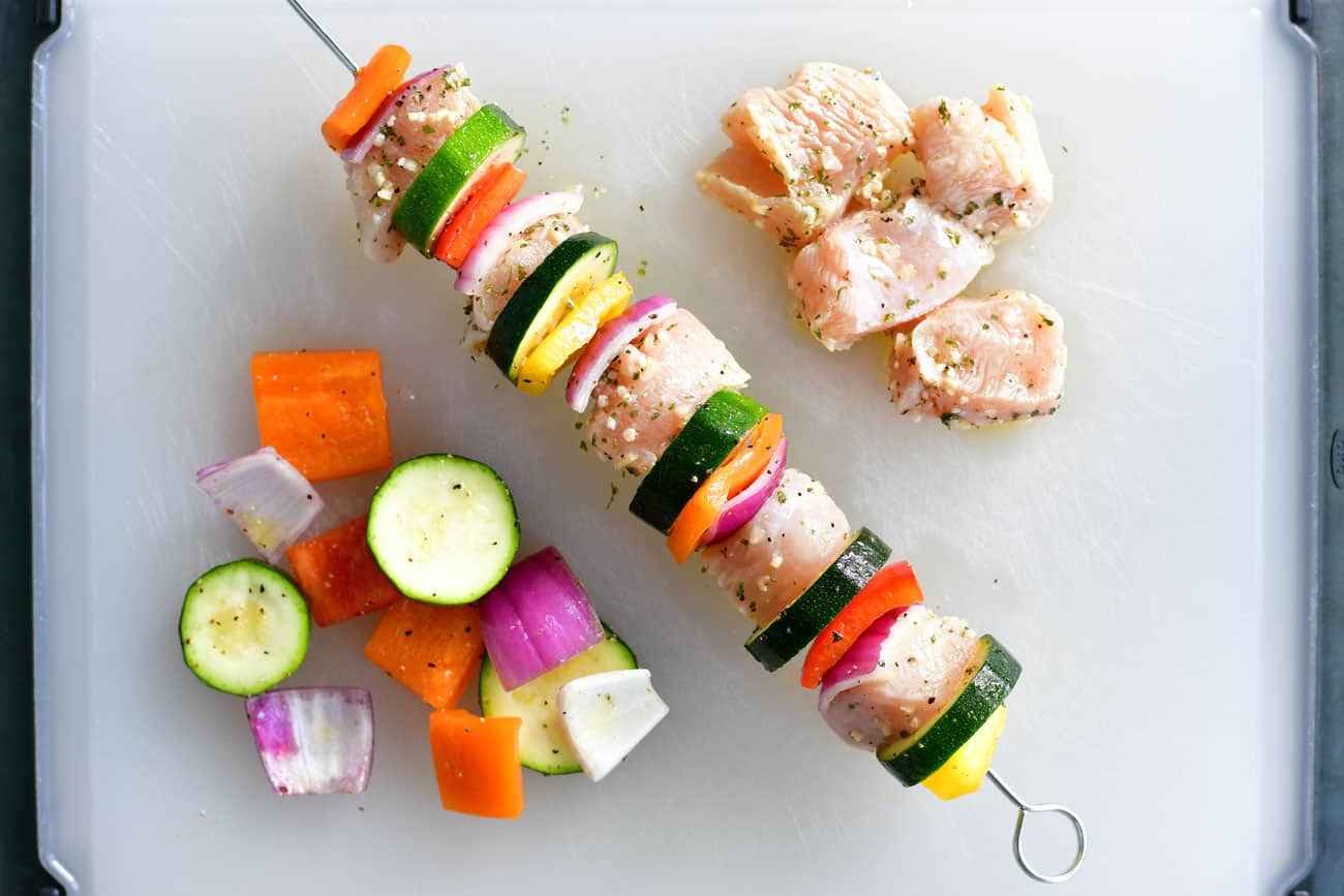 threading raw chicken and sliced veggies onto a metal skewer