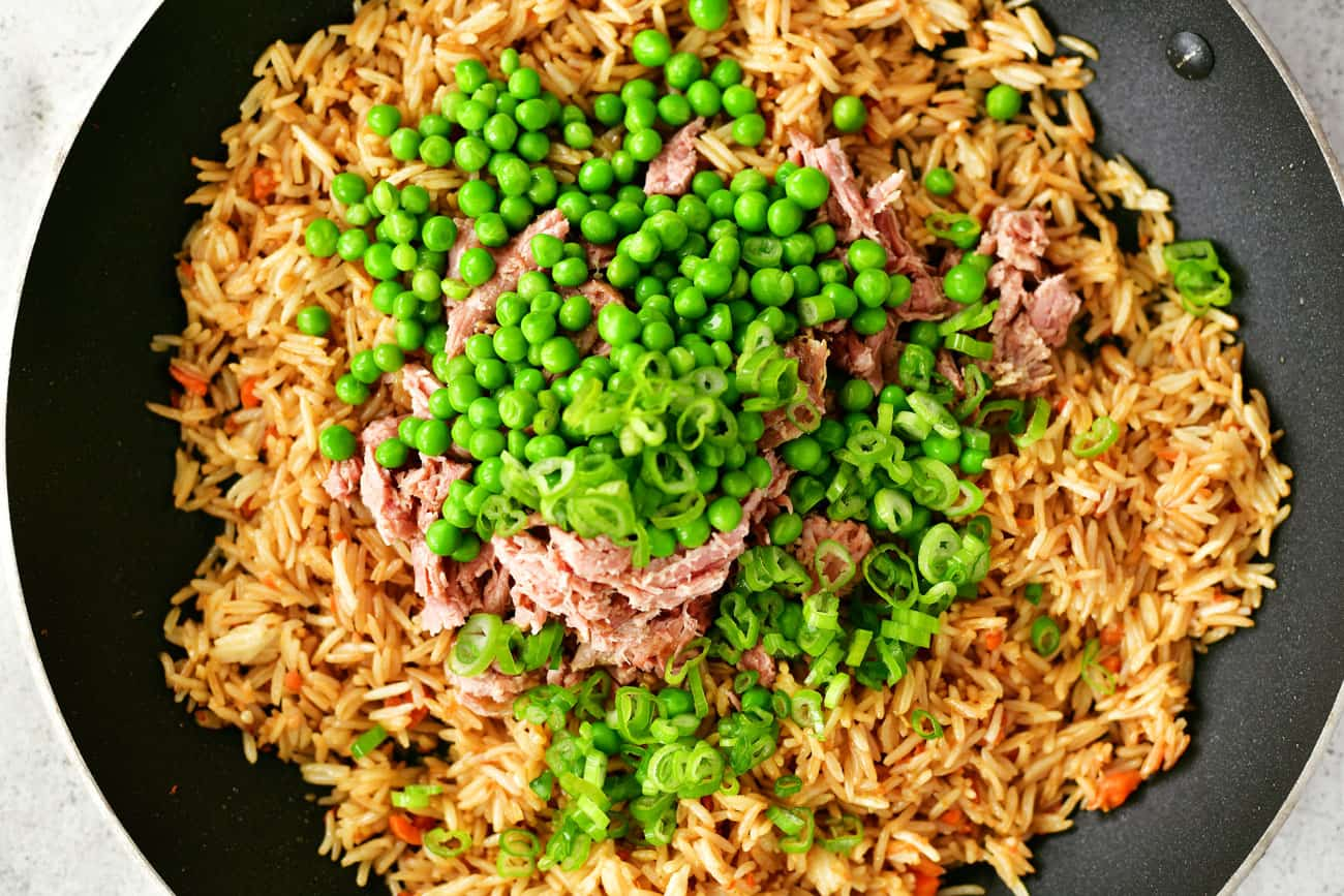pork, peas and onions in saute pan with rice