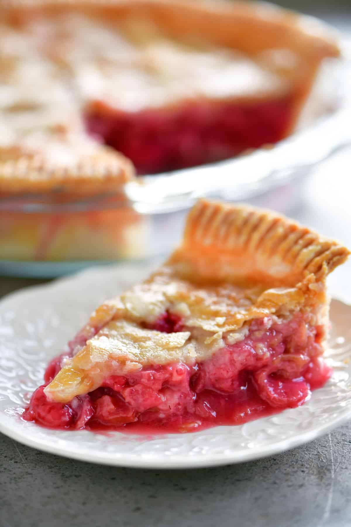slice of strawberry rhubarb pie on white plate