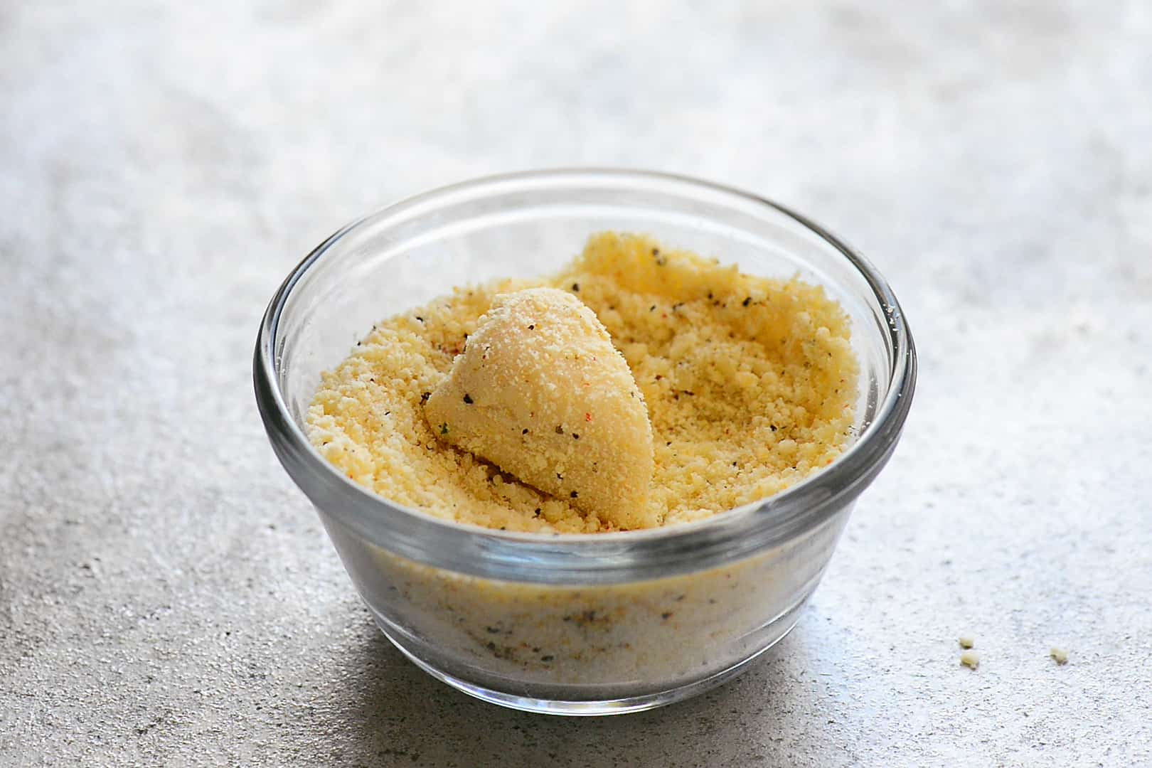 a piece of dough in a parmesan mixture