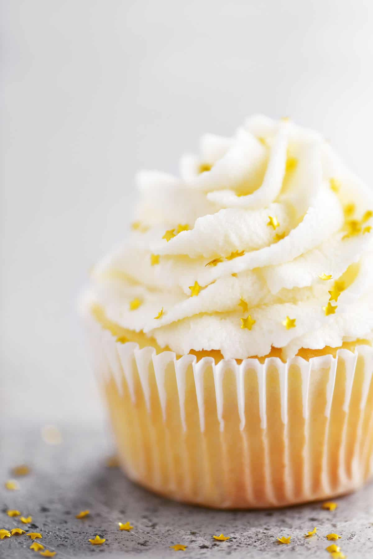 vanilla cupcake with buttercream frosting and gold star sprinkles