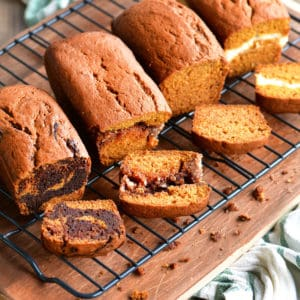 four pumpkin bread loaves on a cooling rack