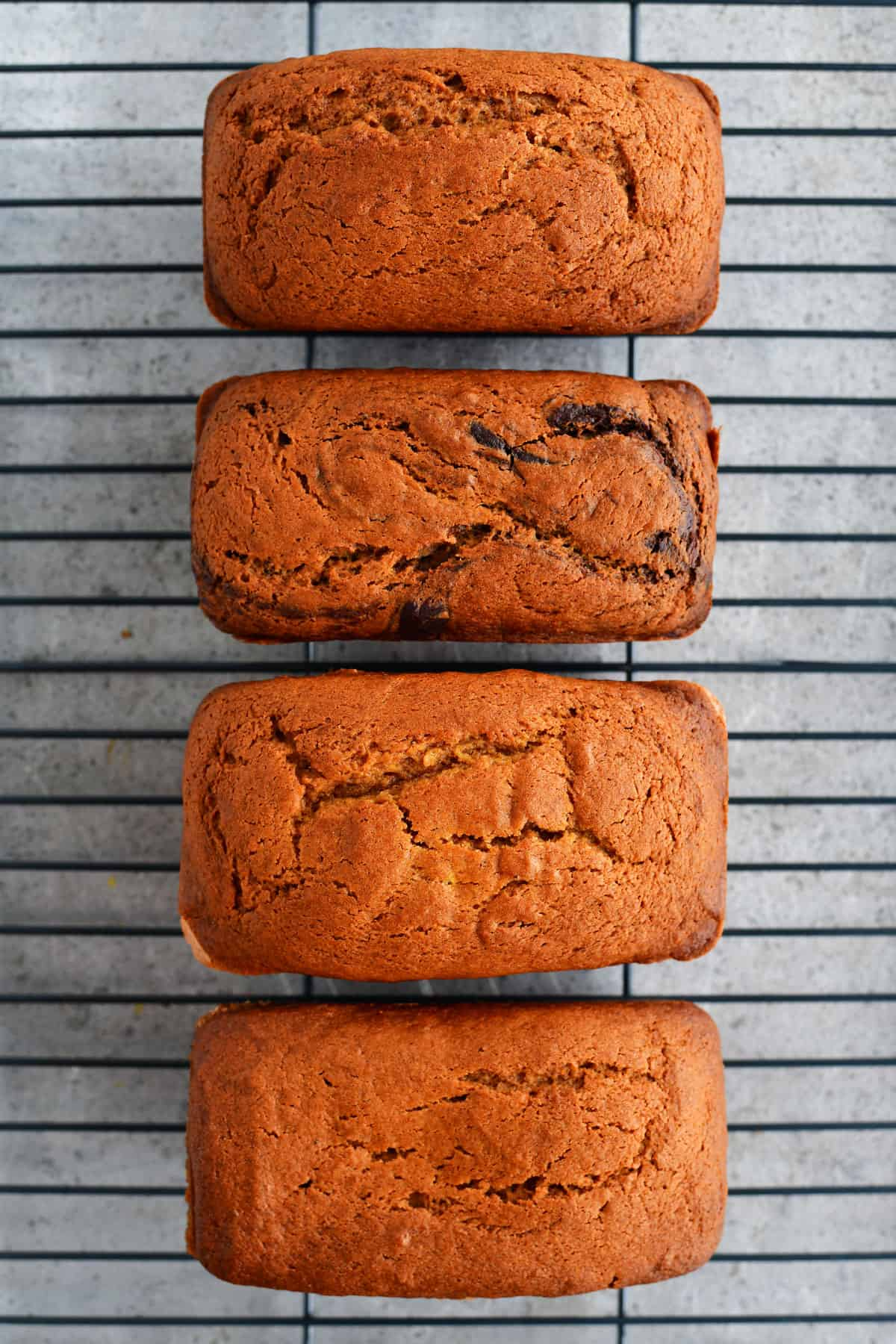 four pumpkin breads on a cooling rack