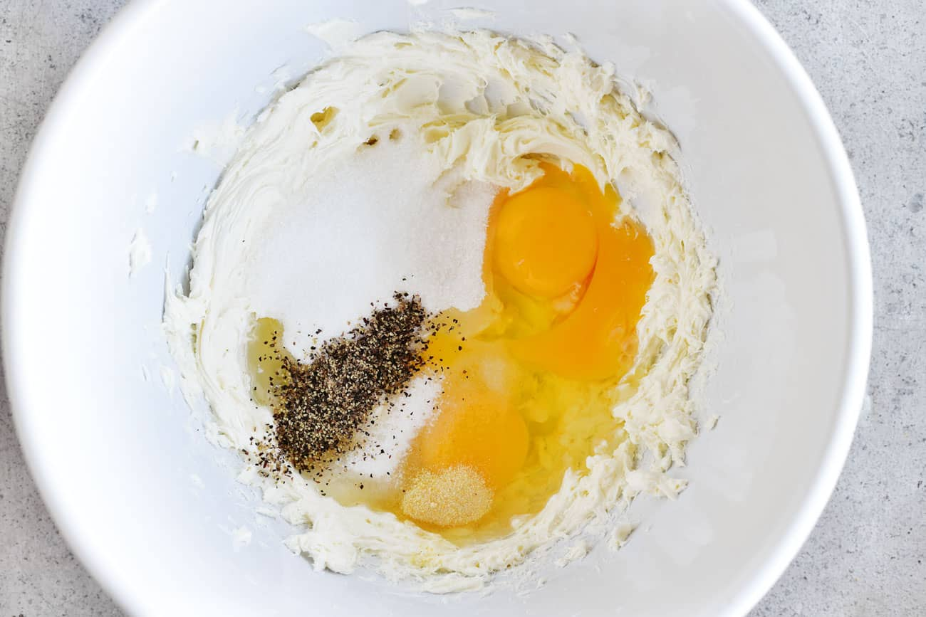 cream cheese, sugar, eggs and pepper in a bowl