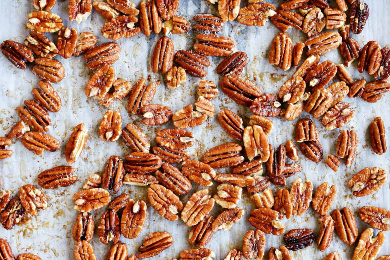 toasted pecans spread out on parchment paper