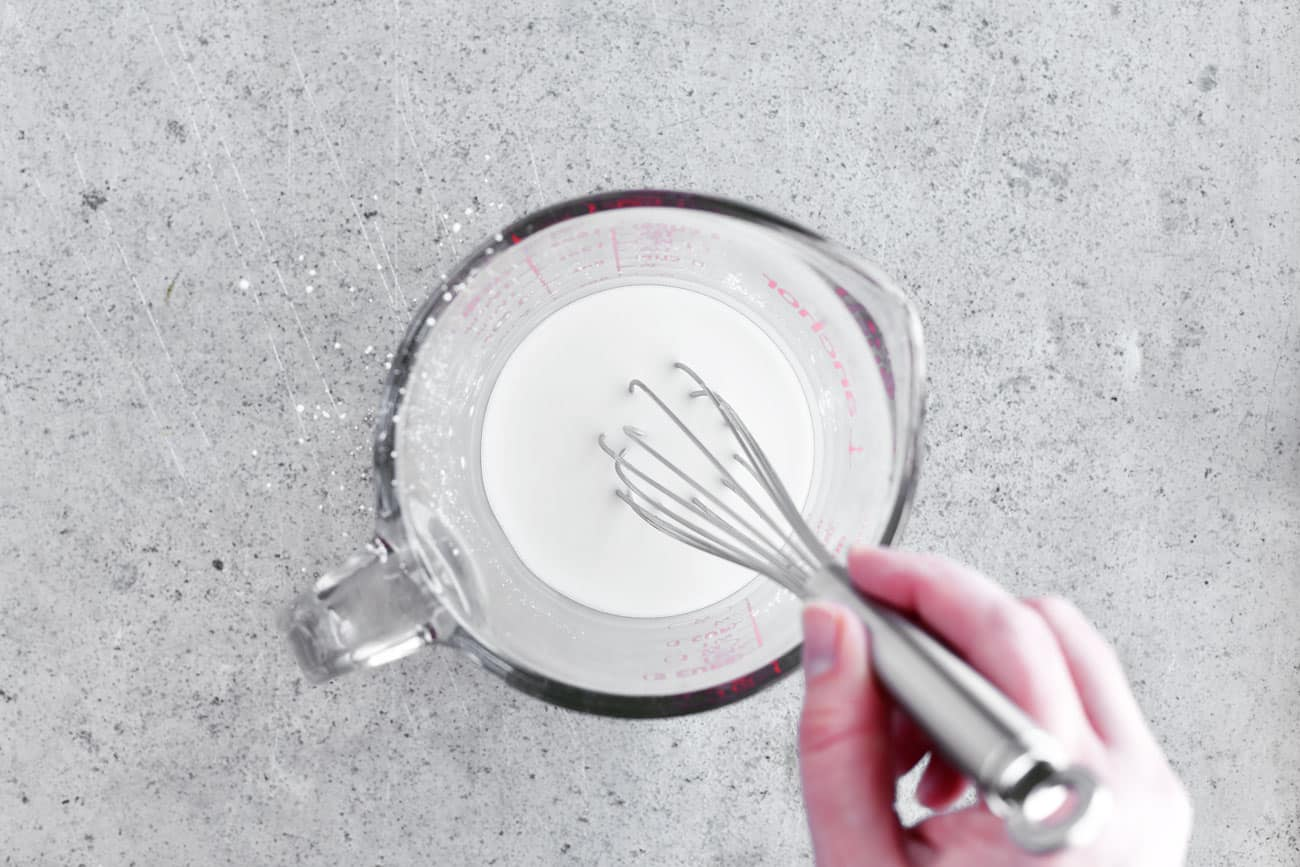 whisking cornstarch and water in a glass bowl