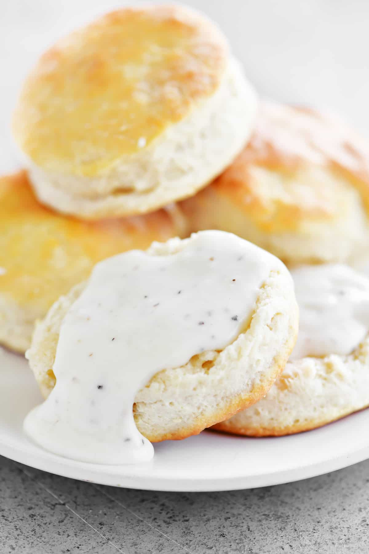 split biscuit on a plate with white gravy on top