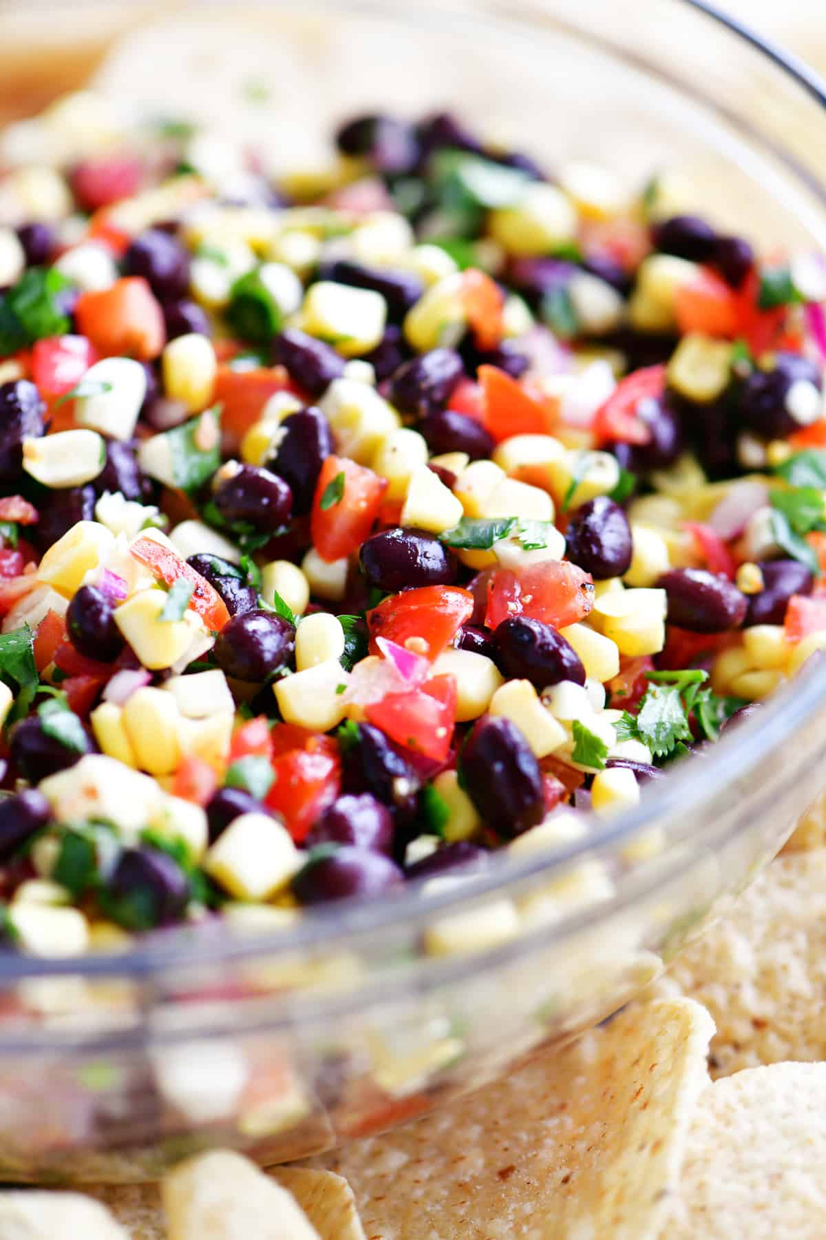black beans and corn salsa in bowl surrounded by chips
