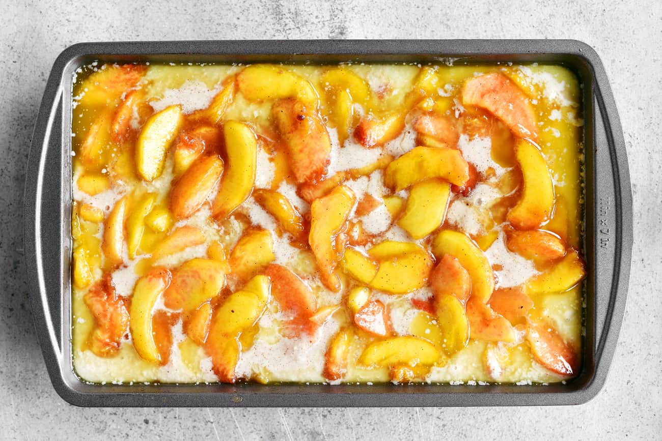 sliced peaches and bisquick batter in pan