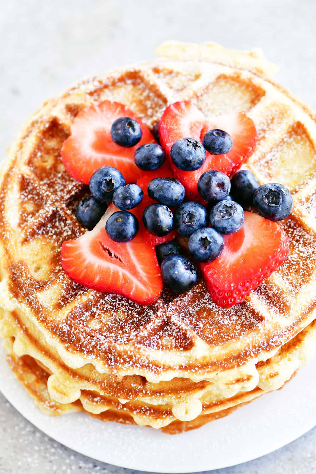 blueberries and strawberries on a stack of waffles