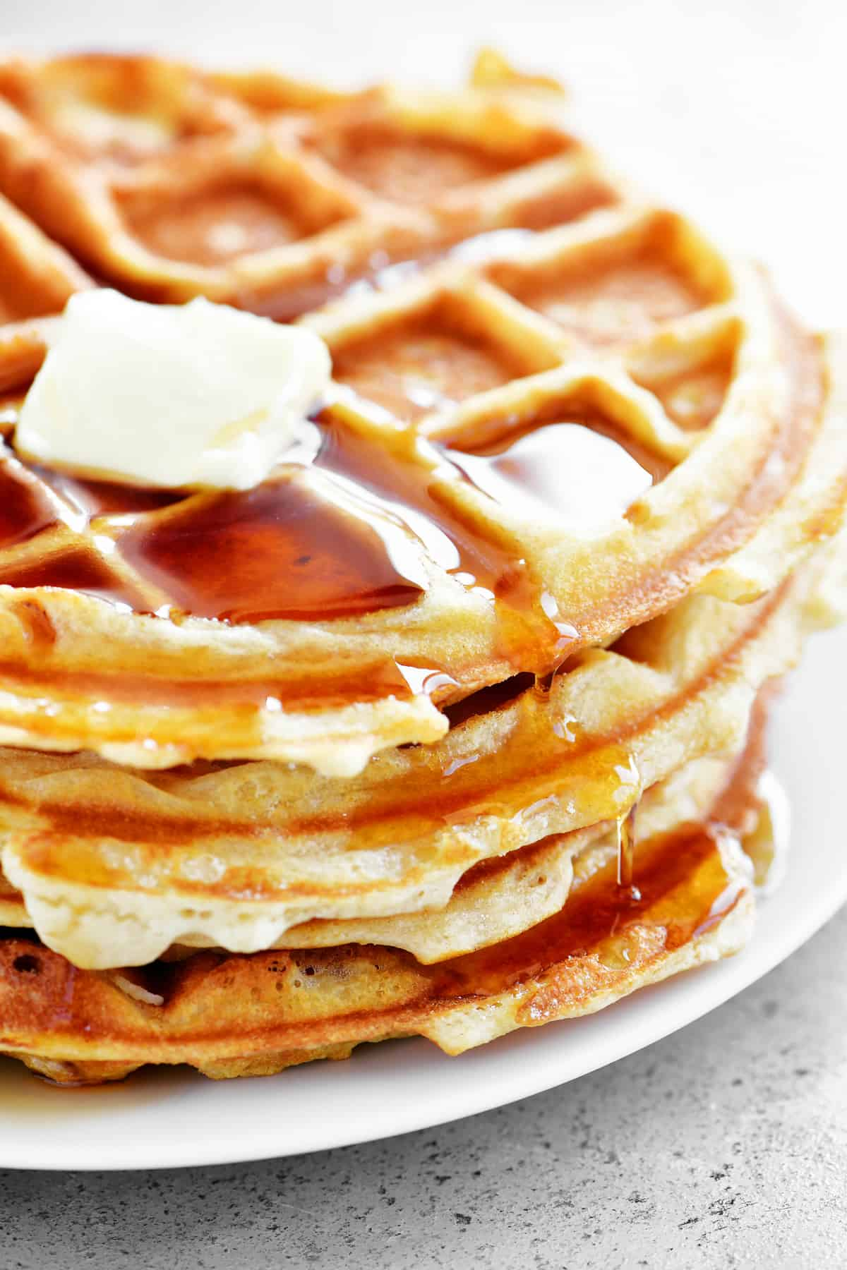 butter and syrup on a stack of waffles