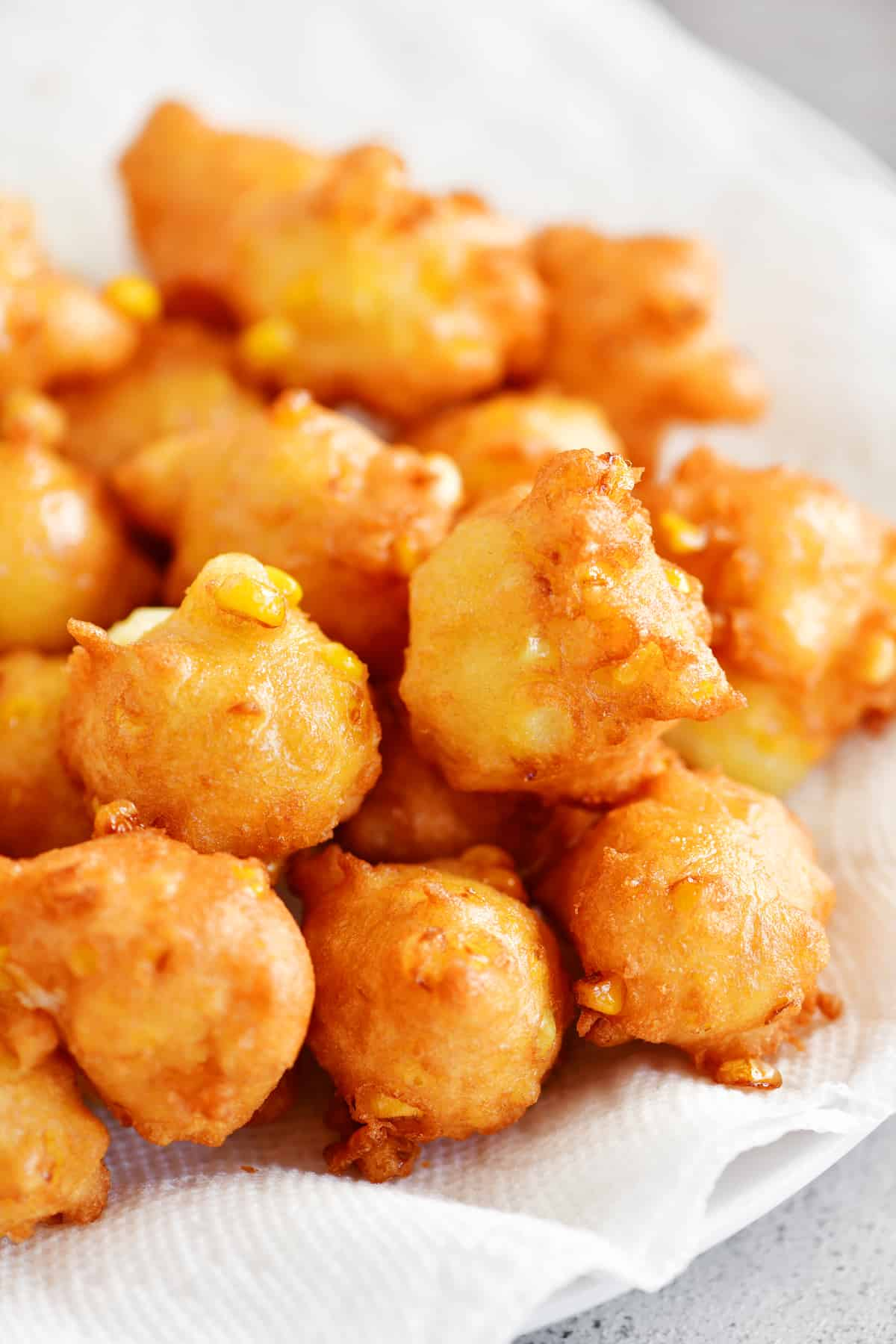 corn fritters draining on paper towels