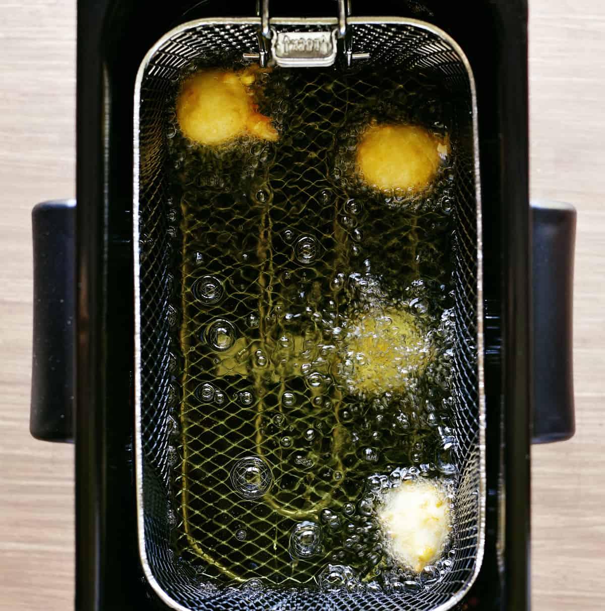 corn fritters frying in oil