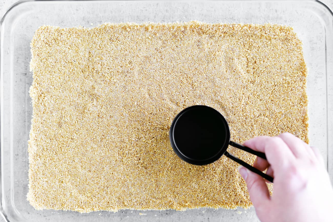 flattening graham cracker crust with measuring cup