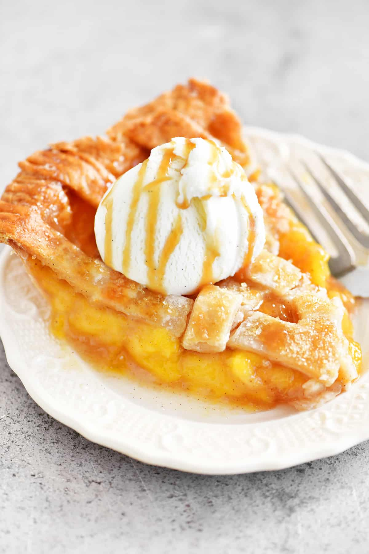 slice of peach pie with ice cream on top