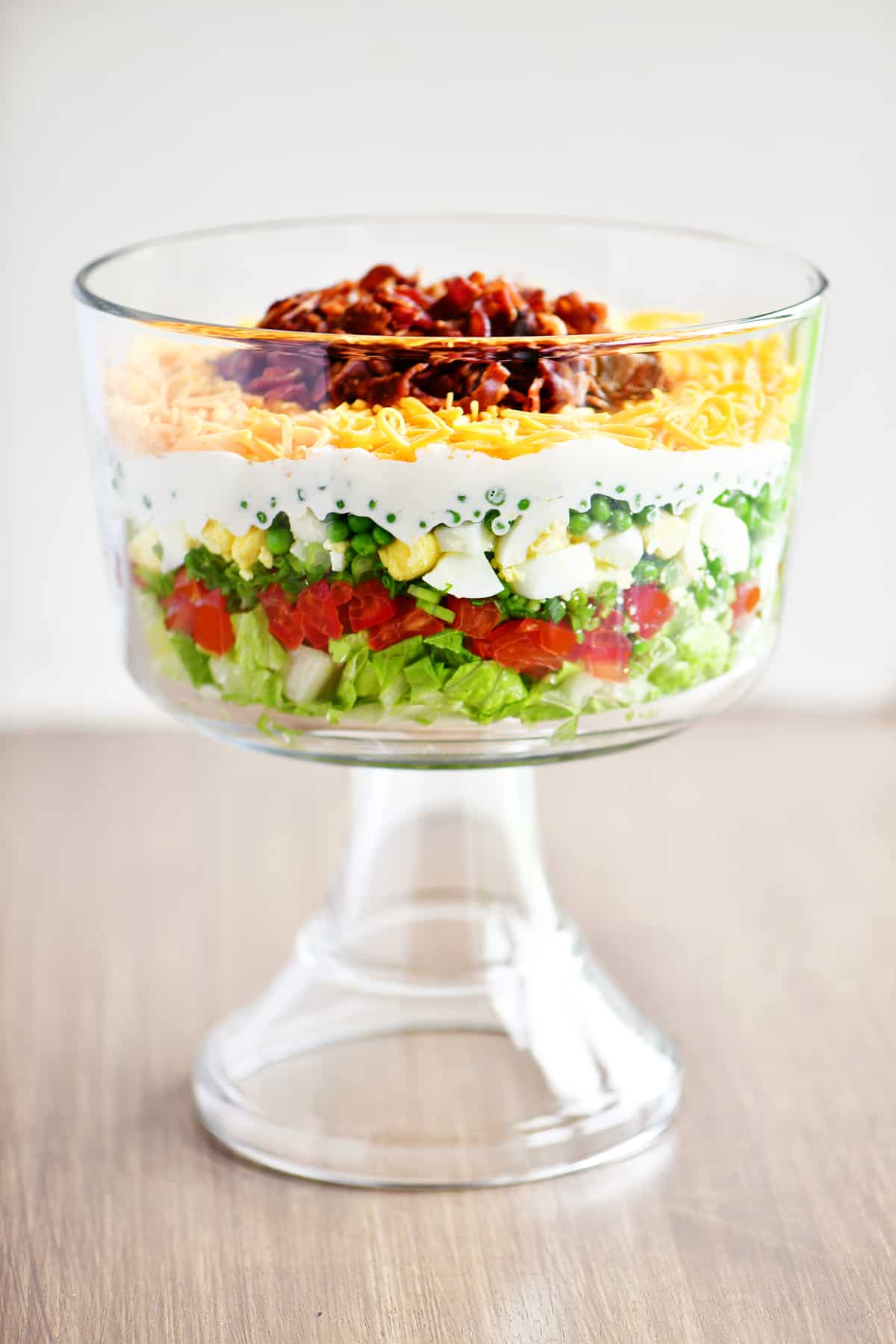 7 layer salad in glass trifle bowl