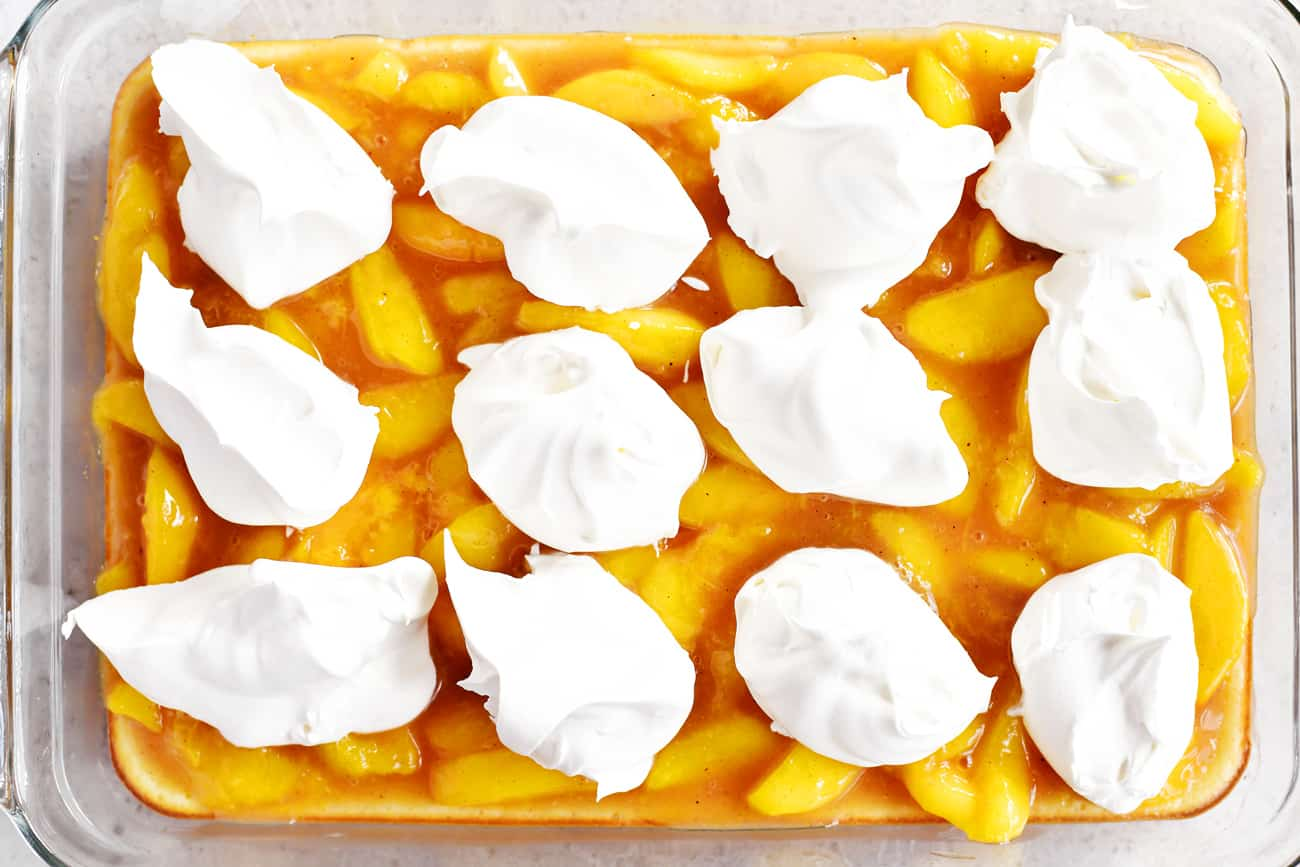 dollops of whipped cream on peach pie filling