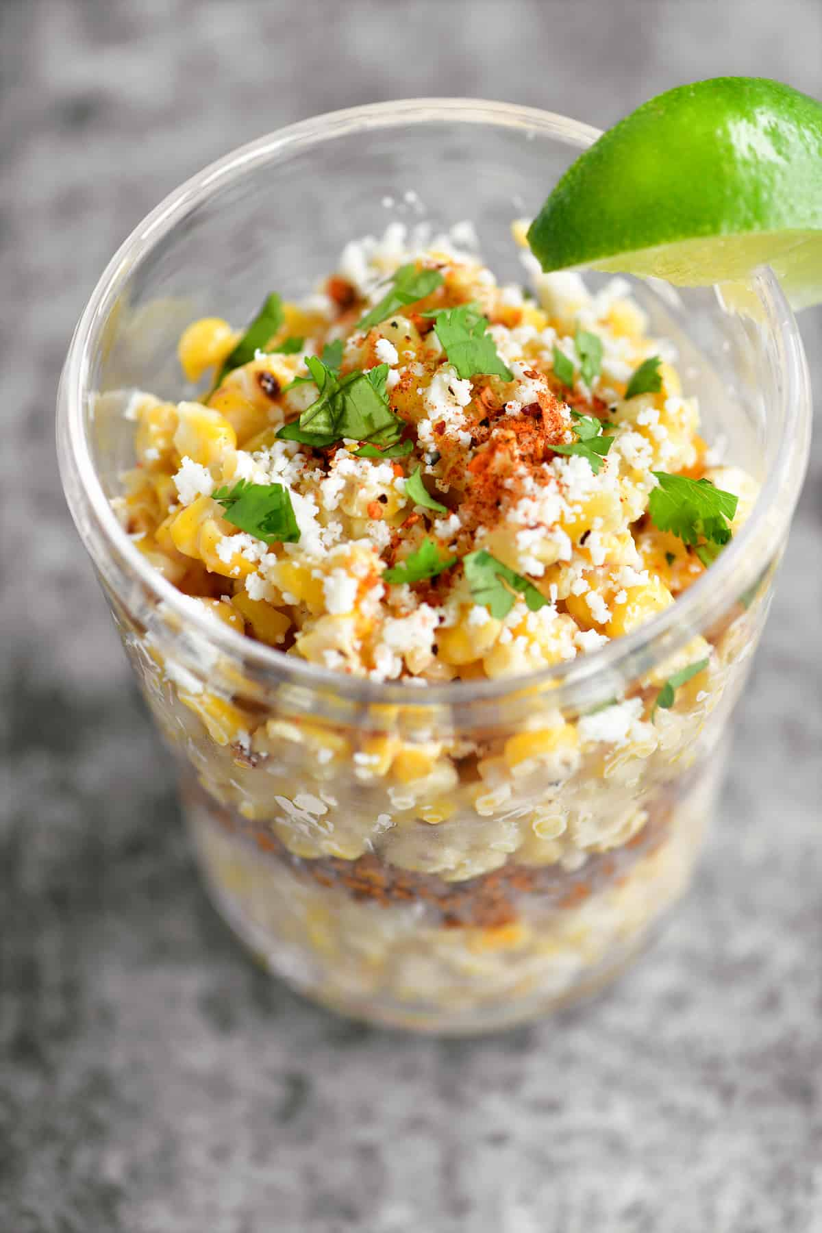 mexican street corn in a cup with seasoning on top
