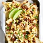 Mexican Street Corn nachos in a tray with lime garnish