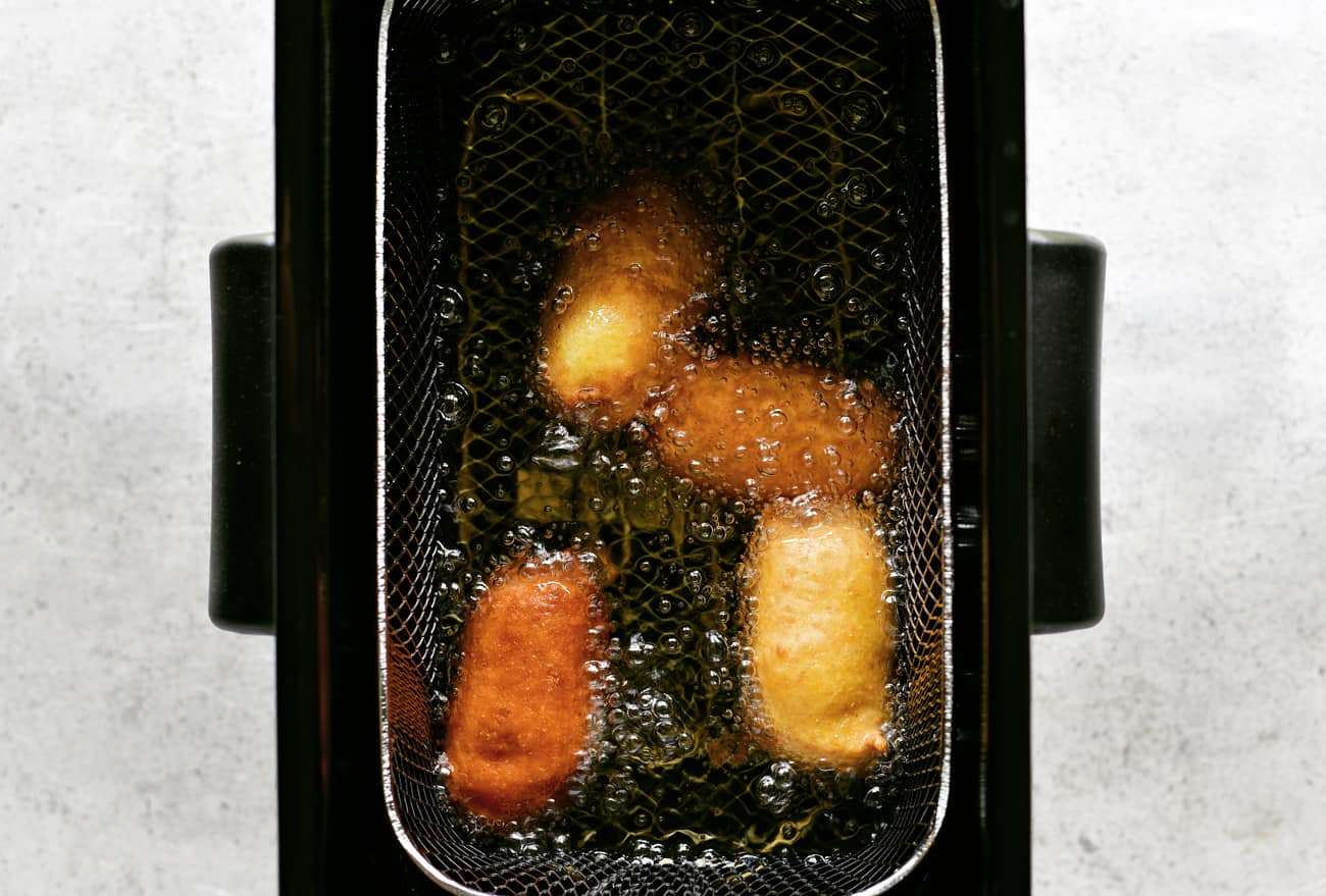 mini corn dogs frying in a fryer