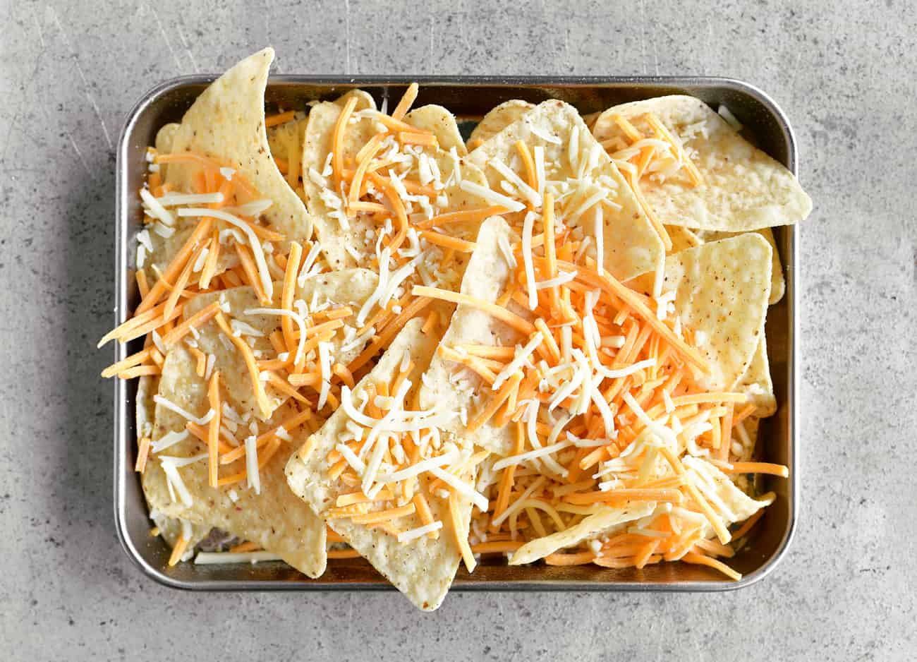 adding shredded cheese to tortilla chips