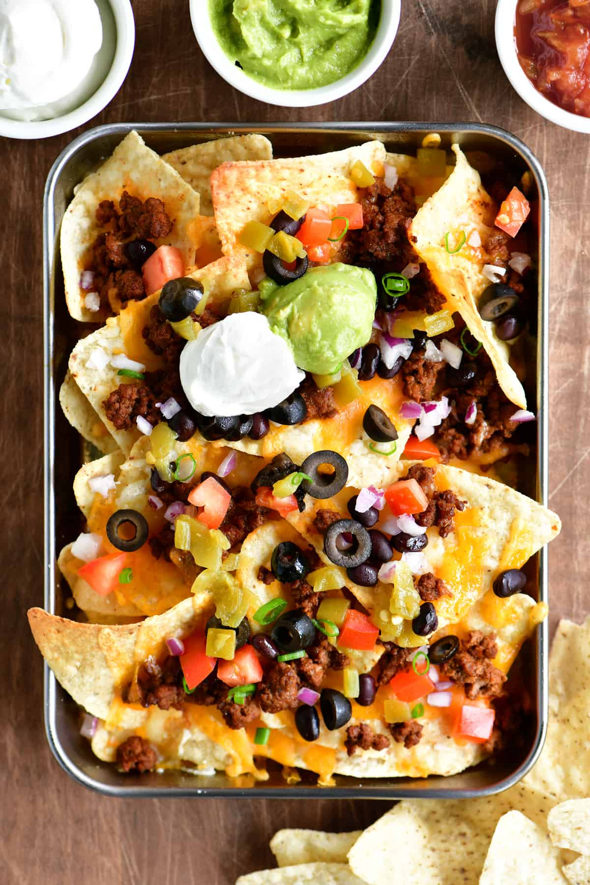 a top-down view of the tray of nachos with sour cream, salsa and guacamole dip in bowls