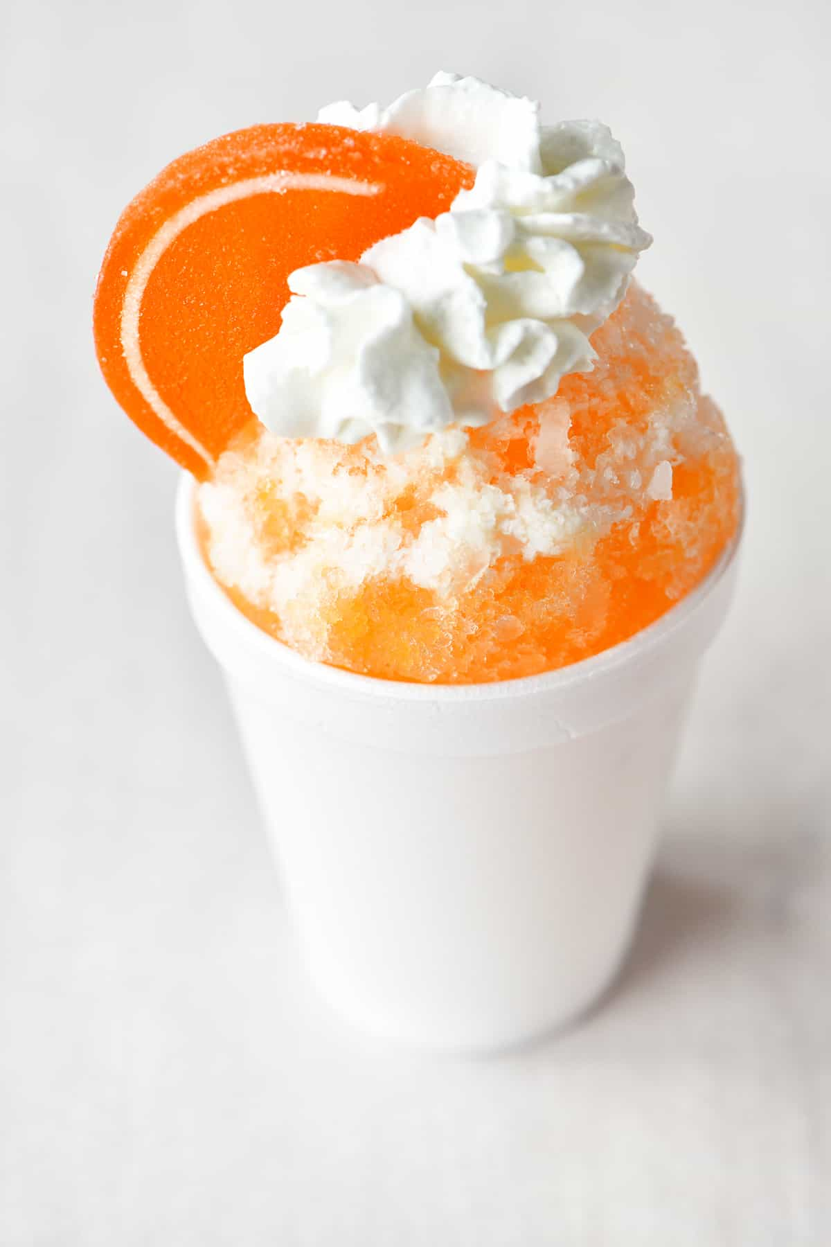 an orange-cream flavored shave ice treat, garnished with a gummy orange slice
