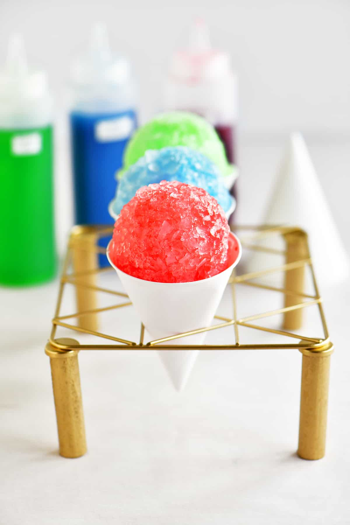 snow cones with snow cone syrup bottles in the background