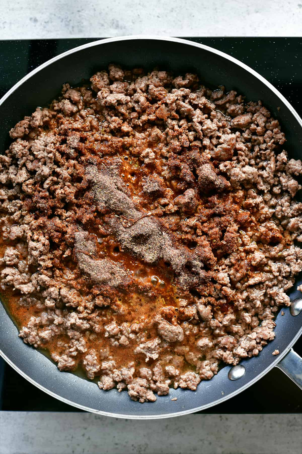 adding taco seasoning to cooked ground beef