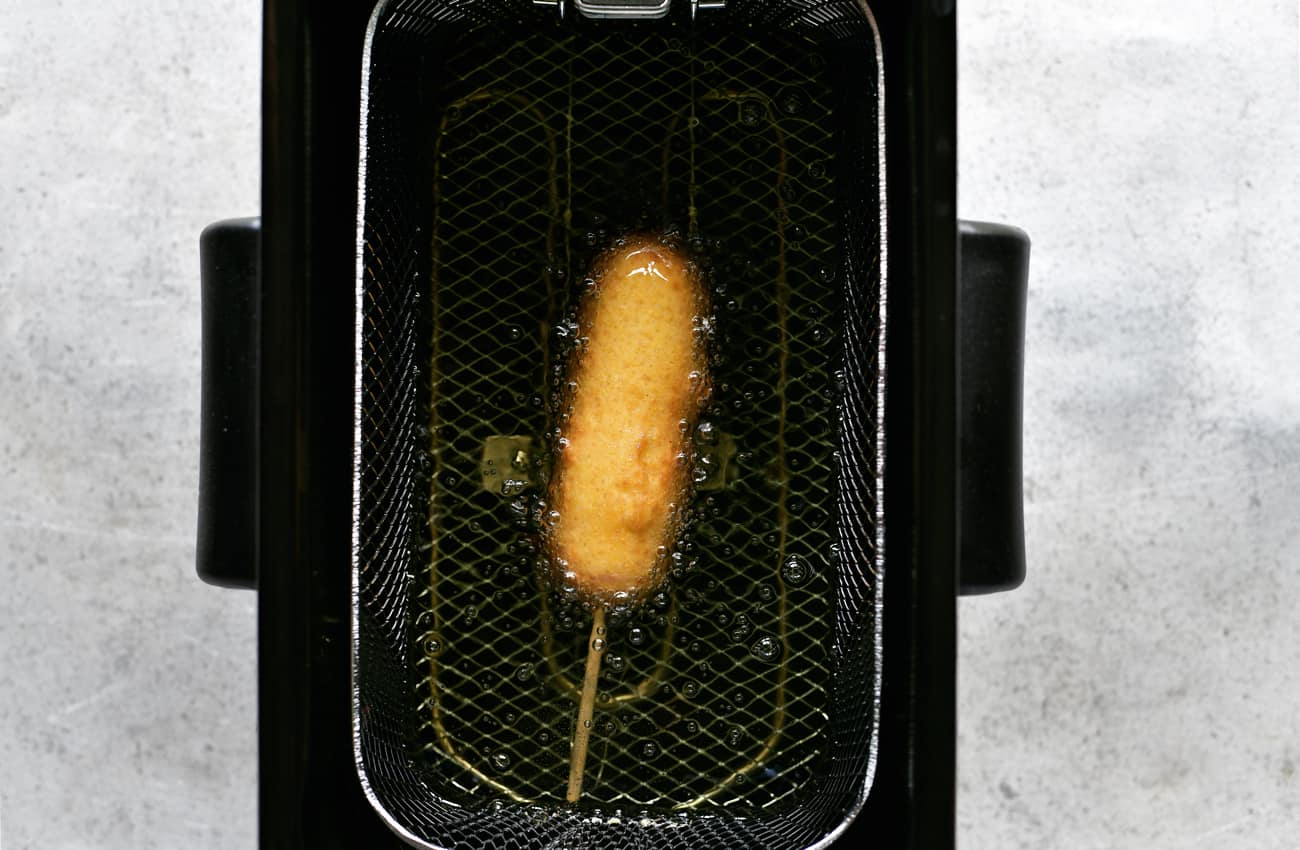 cheese on a stick frying in the fryer