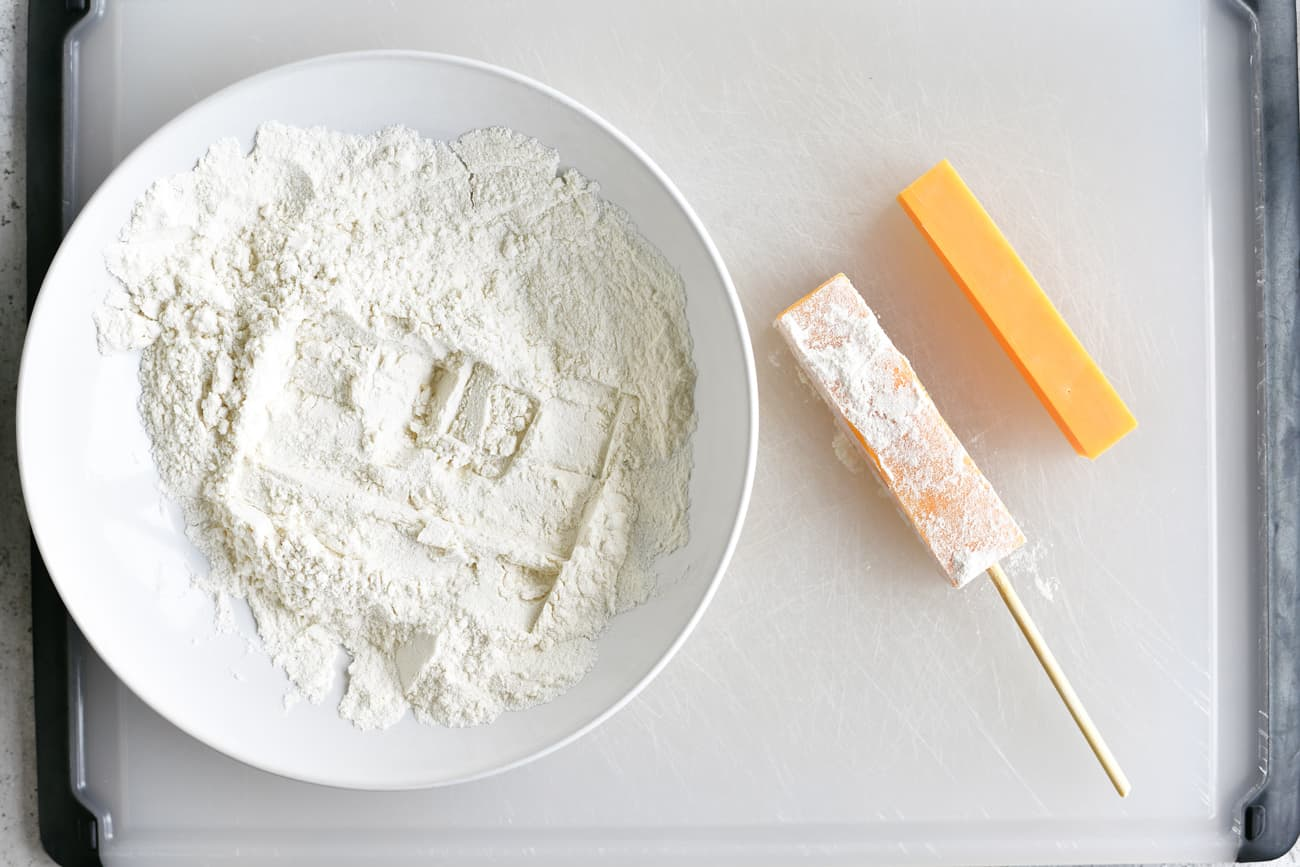 coating cheese on a stick with flour prior to adding batter