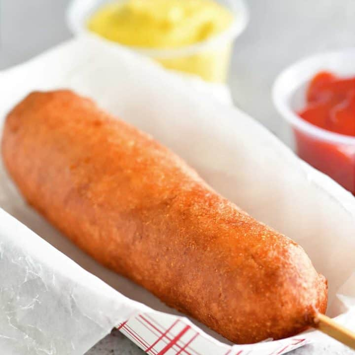 a golden fried corn dog on a red and white paper serving tray