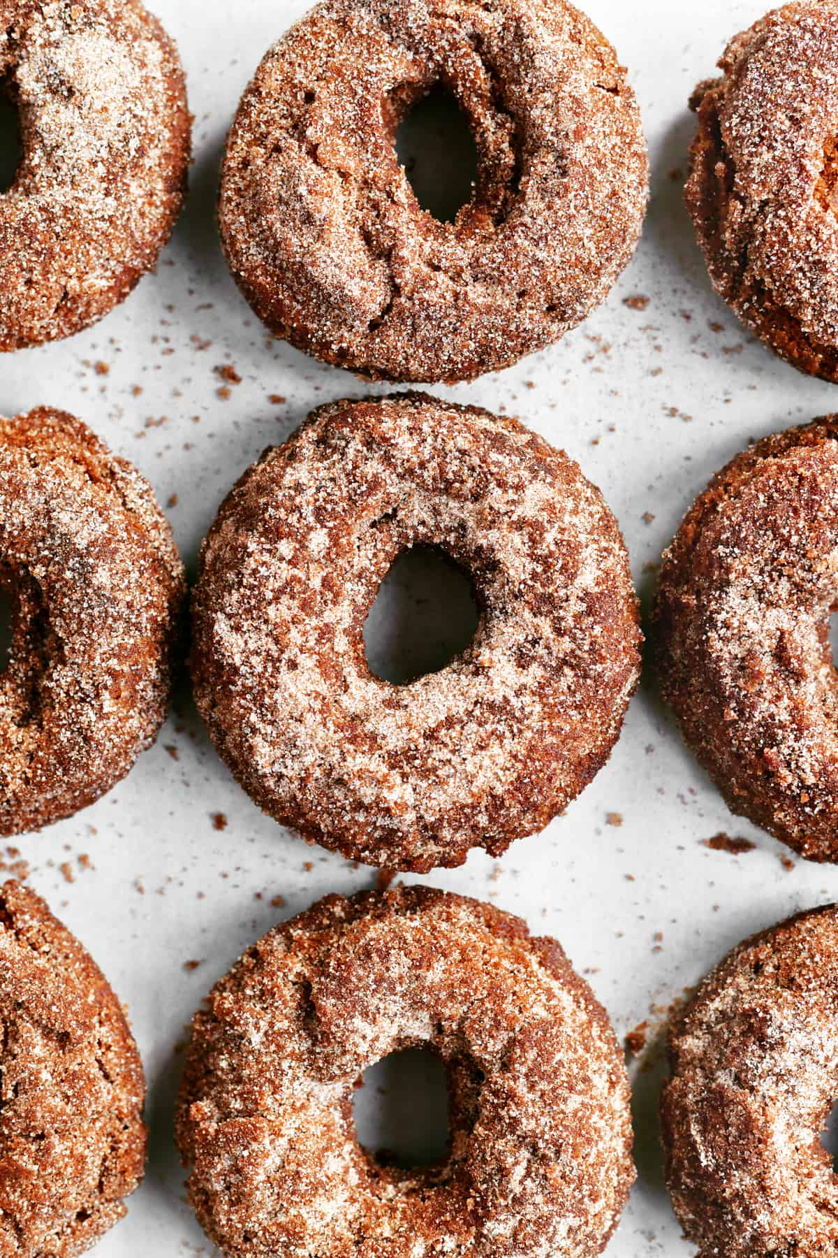 nine apple cider donuts on a baking sheet