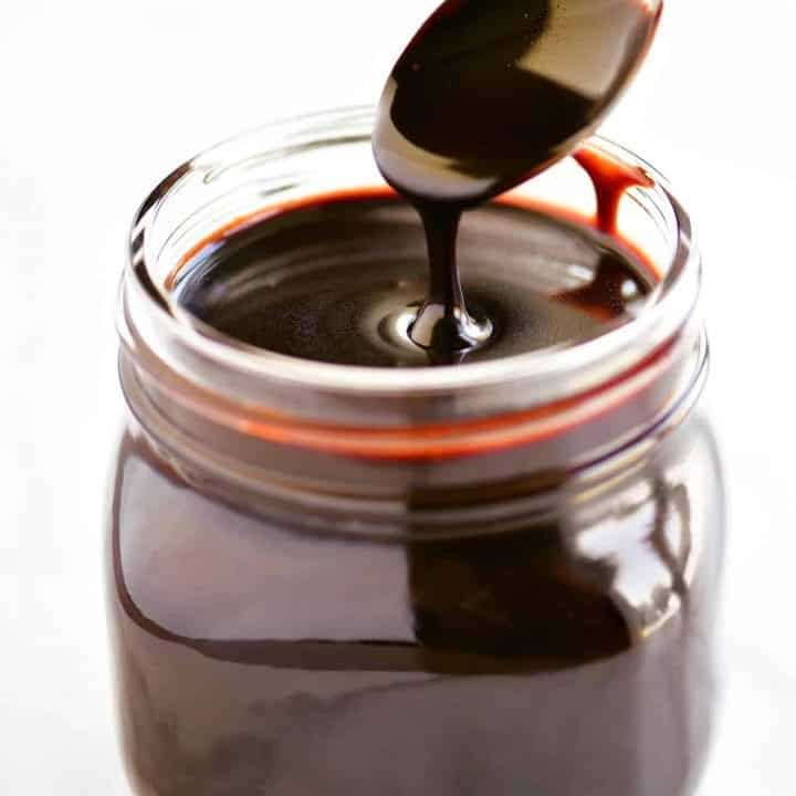 dipping a spoon in a jar of chocolate sauce