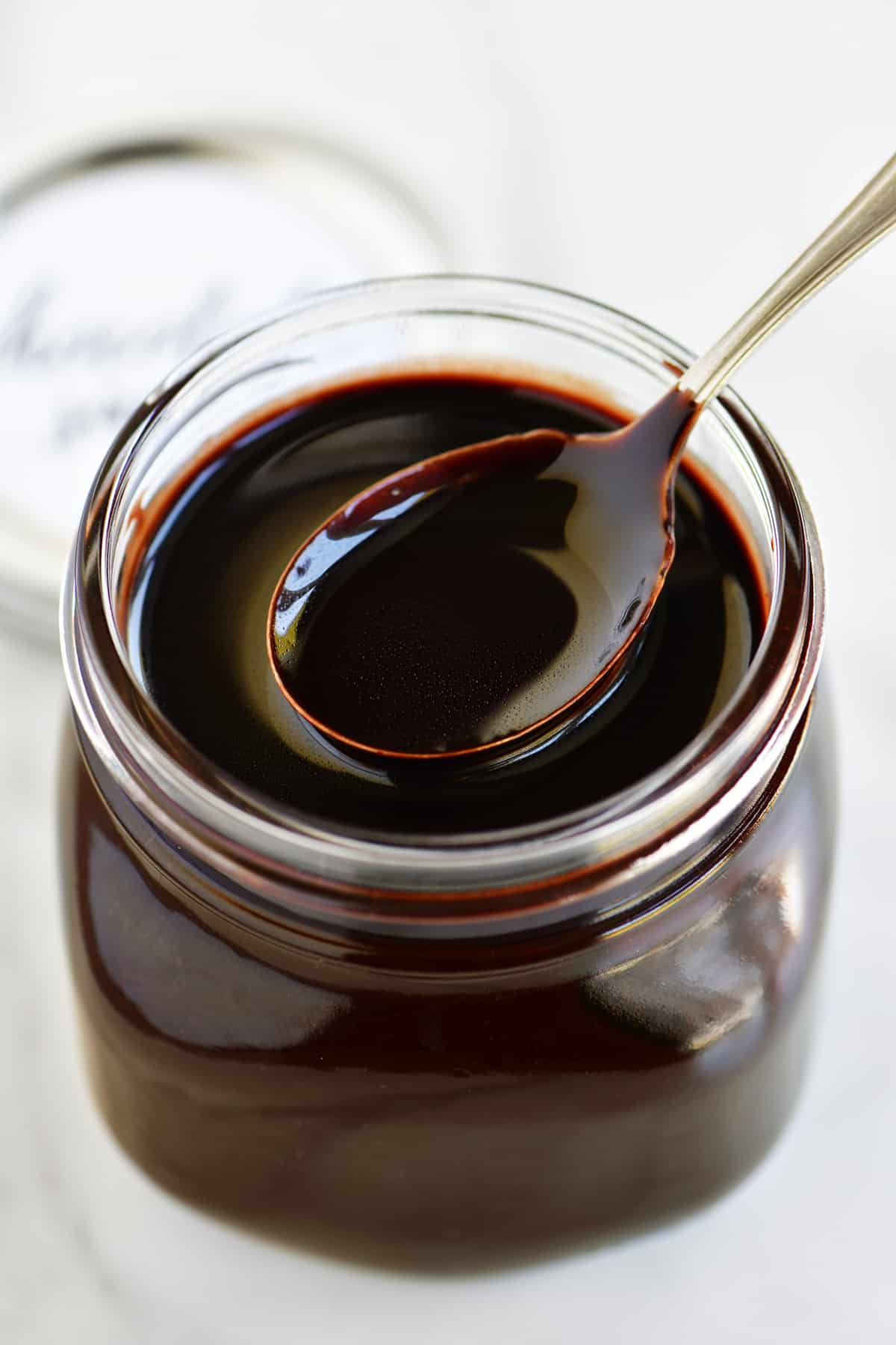 a spoon in a jar of hot chocolate sauce