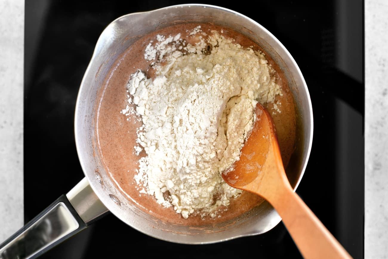adding flour to the churro ingredients