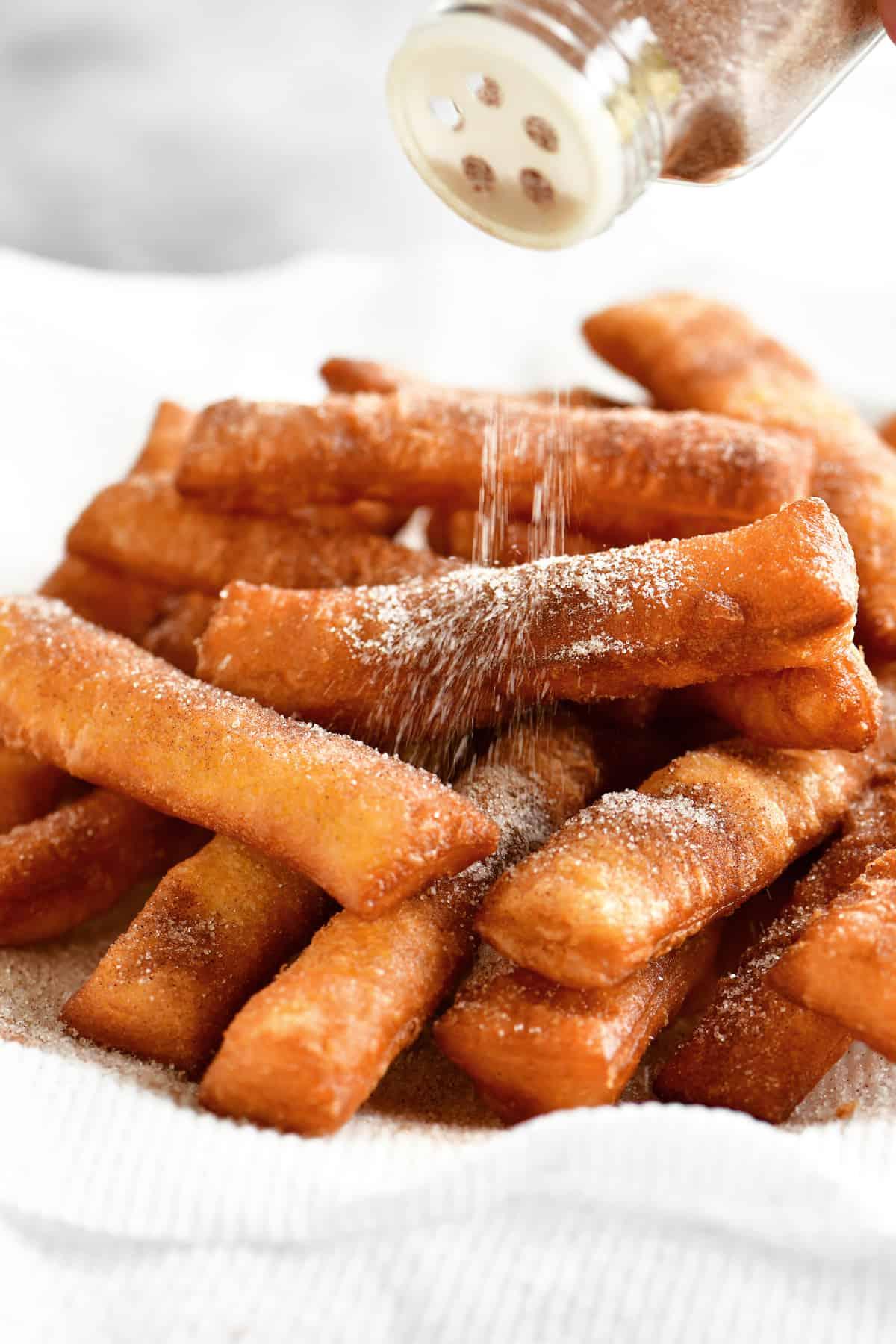 sprinkling cinnamon on the donut sticks