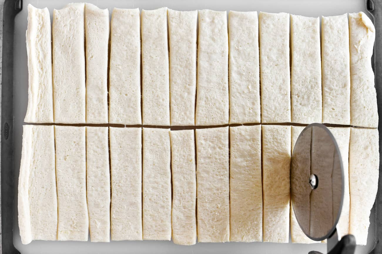 cutting the dough into strips with a pizza wheel