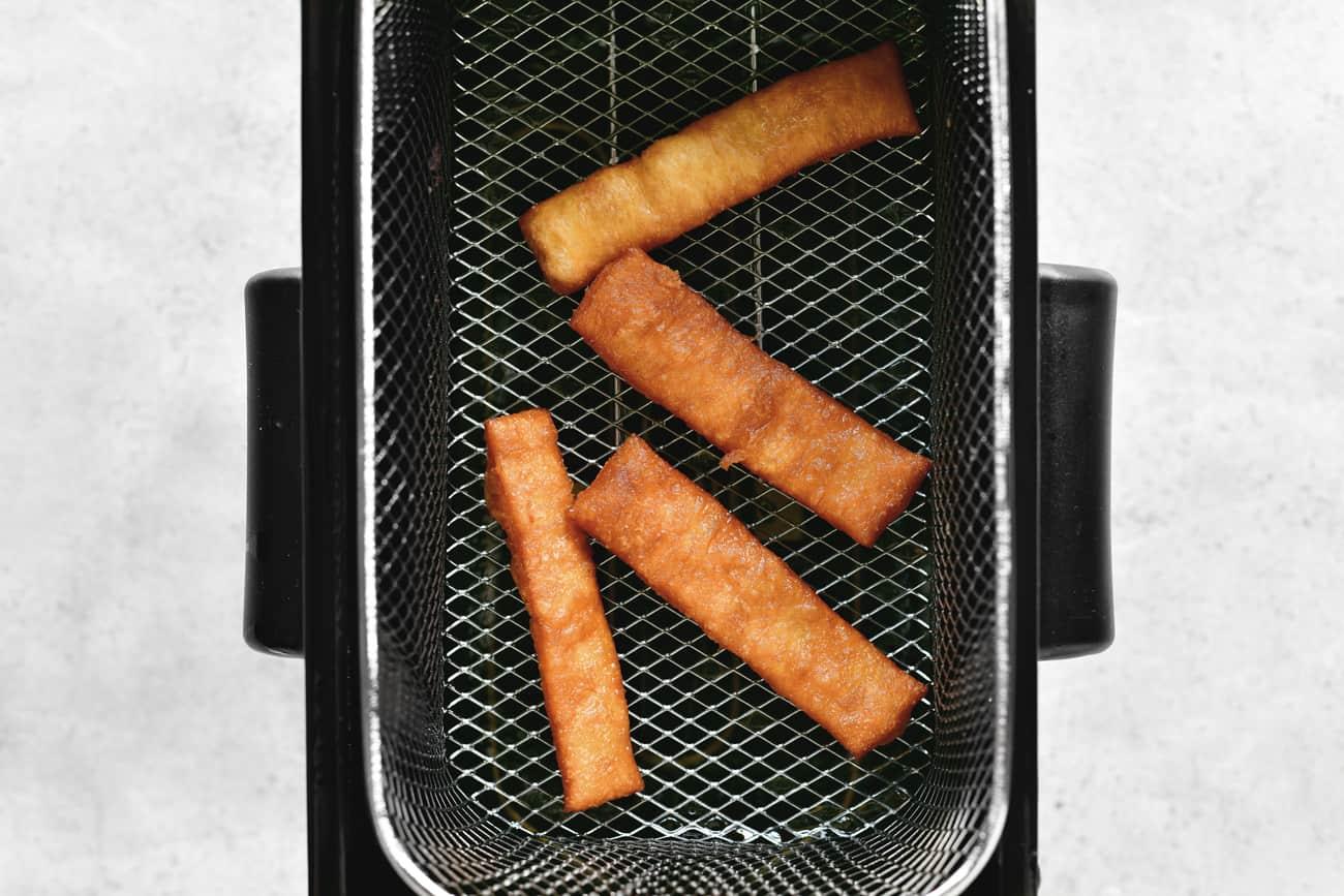 fried donut sticks in the fryer basket