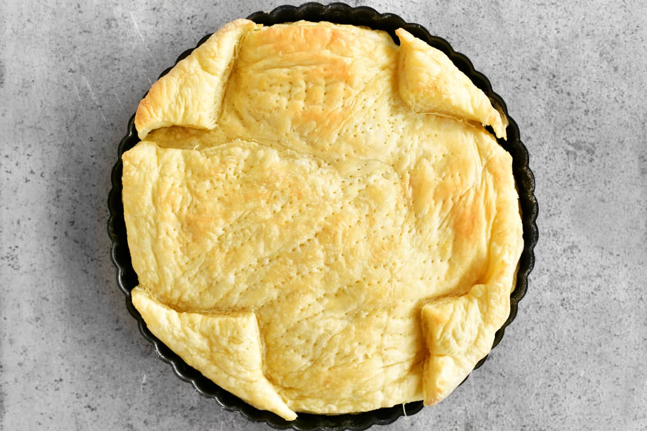 a golden baked crust in a tart pan fresh out of the oven