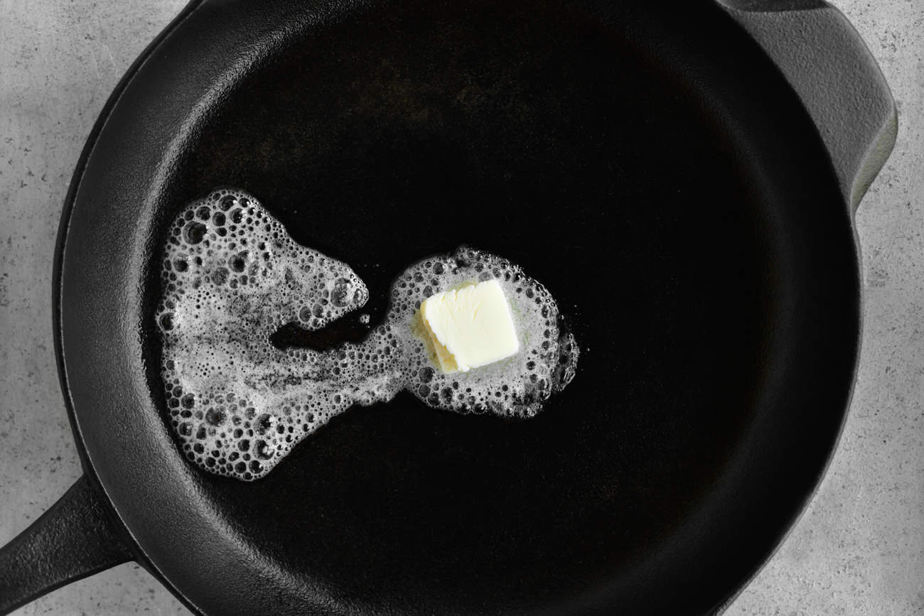 adding a pat of butter to the skillet