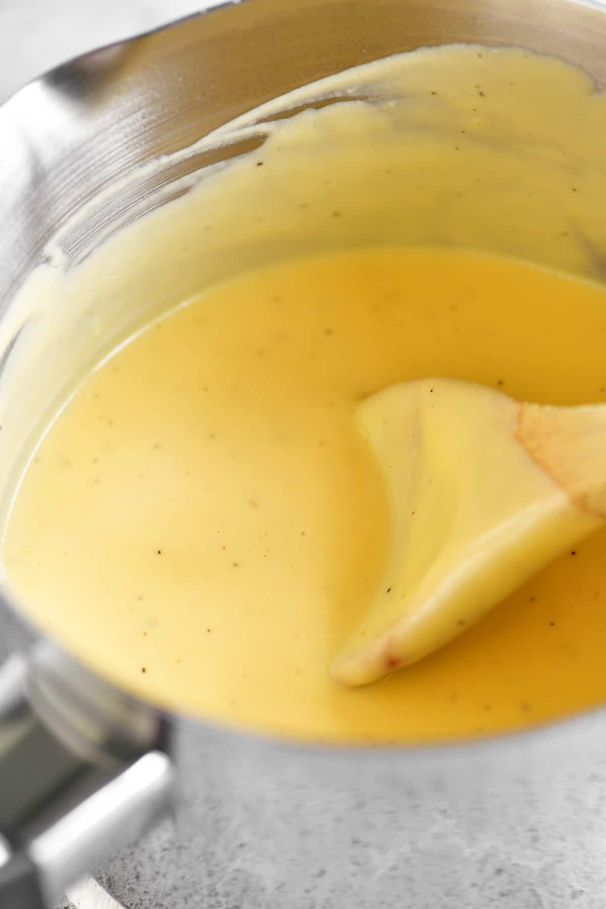 a close-up photo of the cheese sauce in the saucepan