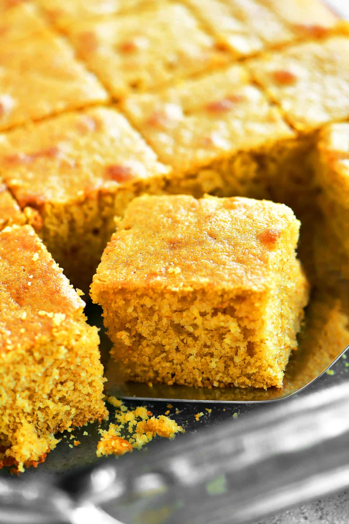 removing a slice of cornbread from the pan