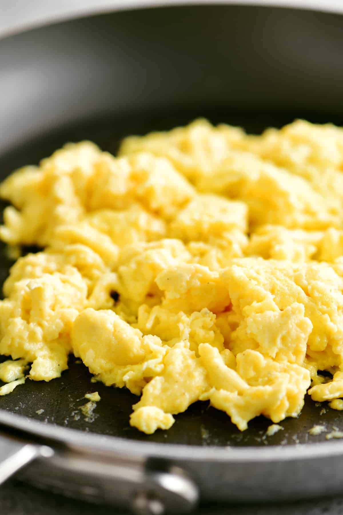 fluffy scrambled eggs in the frying pan