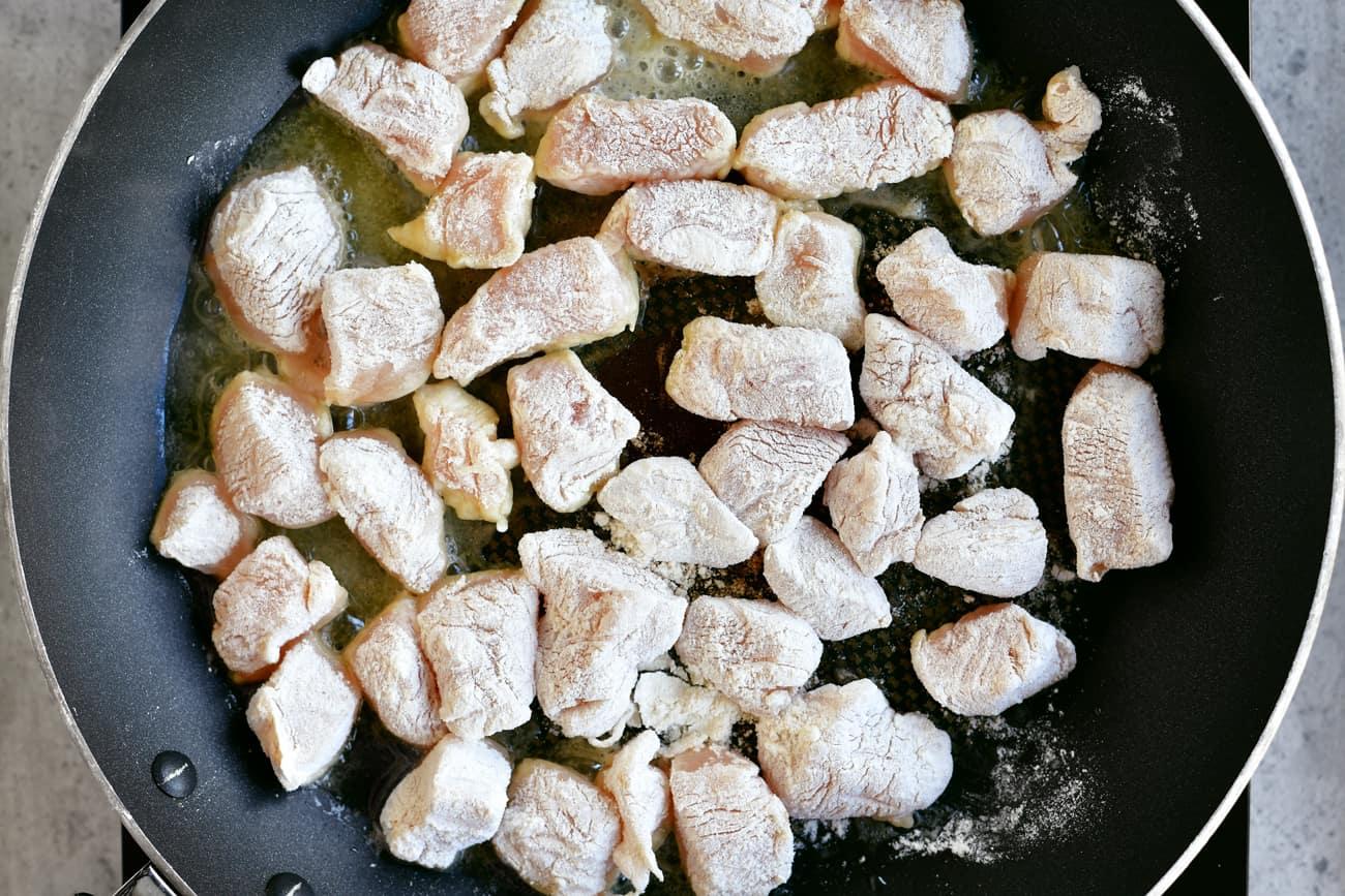 flour coated chicken in skillet