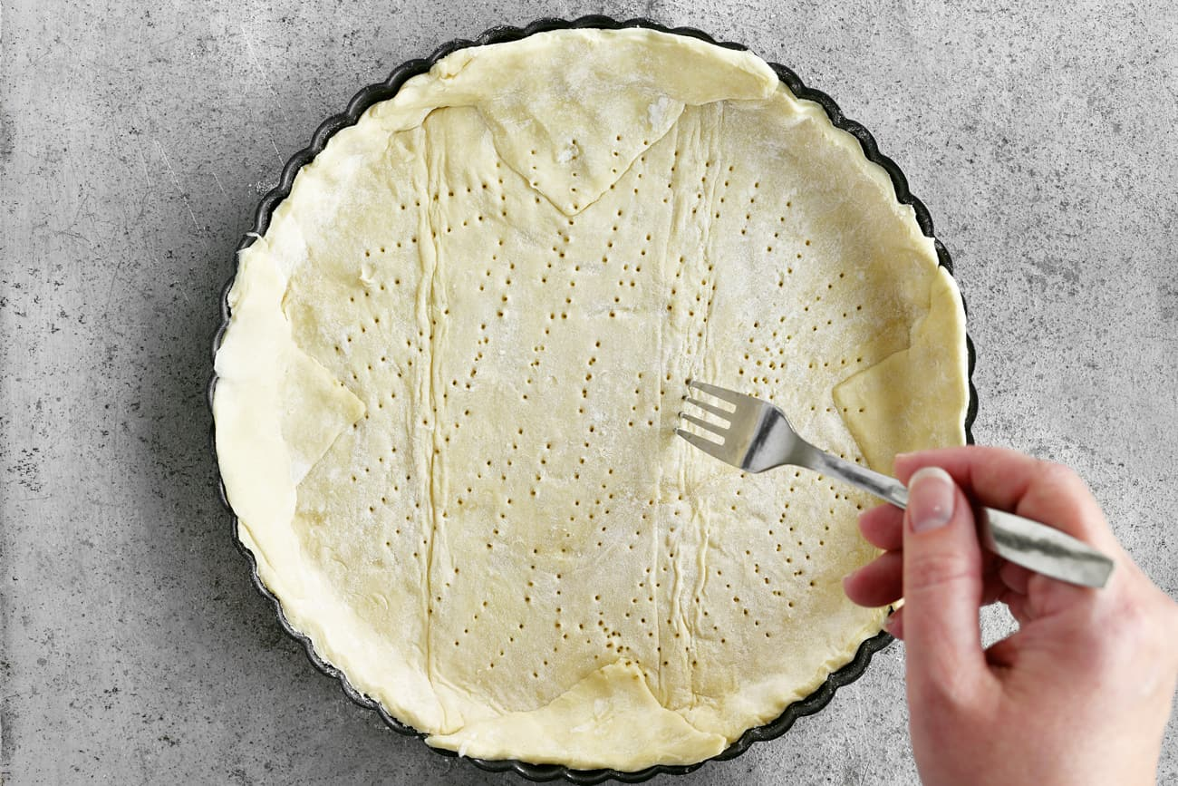 using a fork to perforate the crust dough prior to cooking
